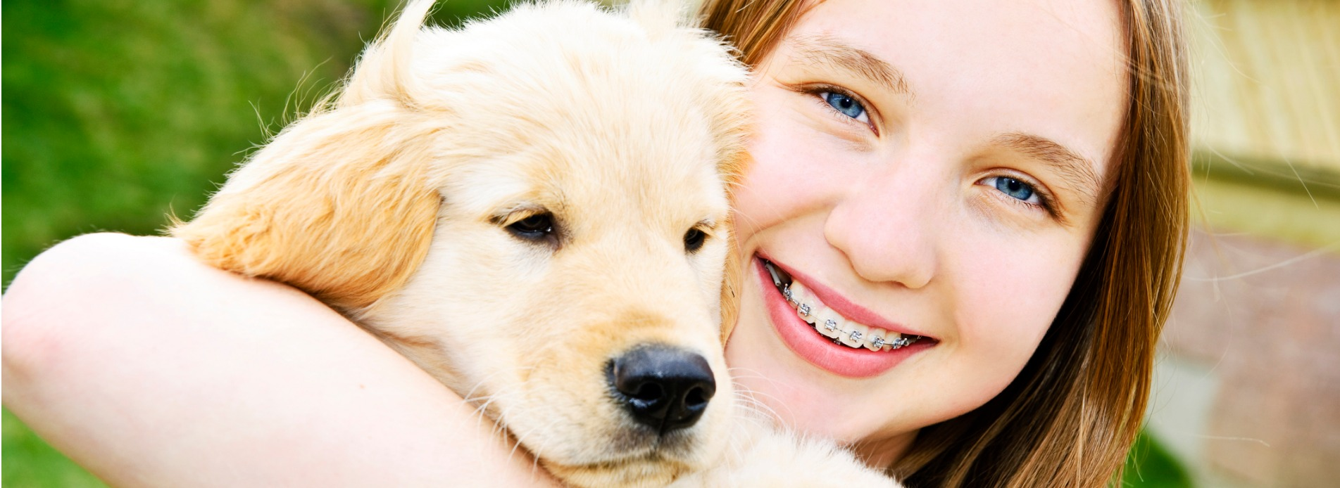 girl smiling holding a puppy dog picture